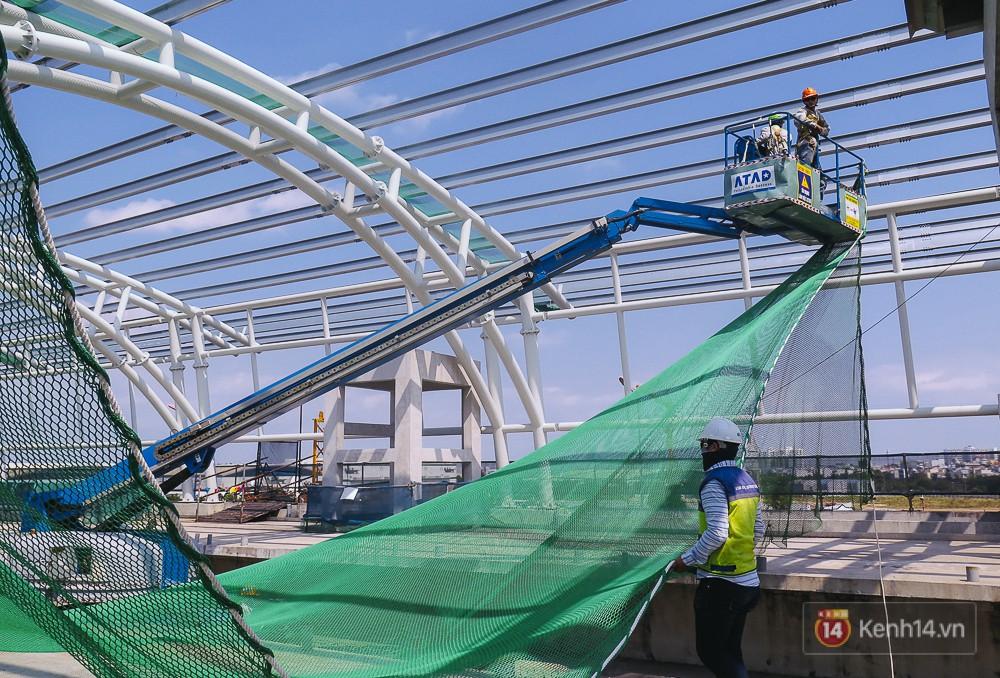 Các công nhân đang giăng lưới trên phần mái để thi công công đoạn tiếp theo.