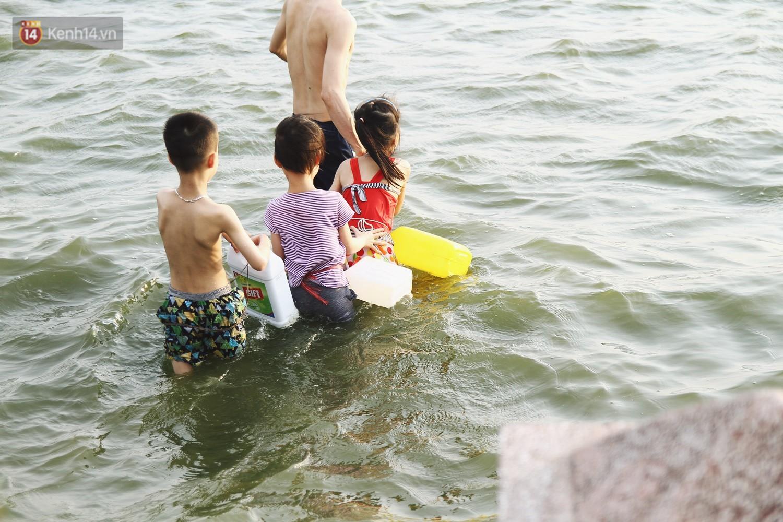 Nắng nóng oi bức, người dân Thủ đô bế chó cưng ra Hồ Tây cùng tắm để giải nhiệt dù có biển cấm - Ảnh 8.