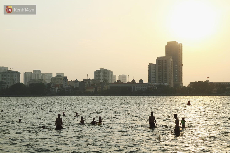 Nắng nóng oi bức, người dân Thủ đô bế chó cưng ra Hồ Tây cùng tắm để giải nhiệt dù có biển cấm - Ảnh 1.