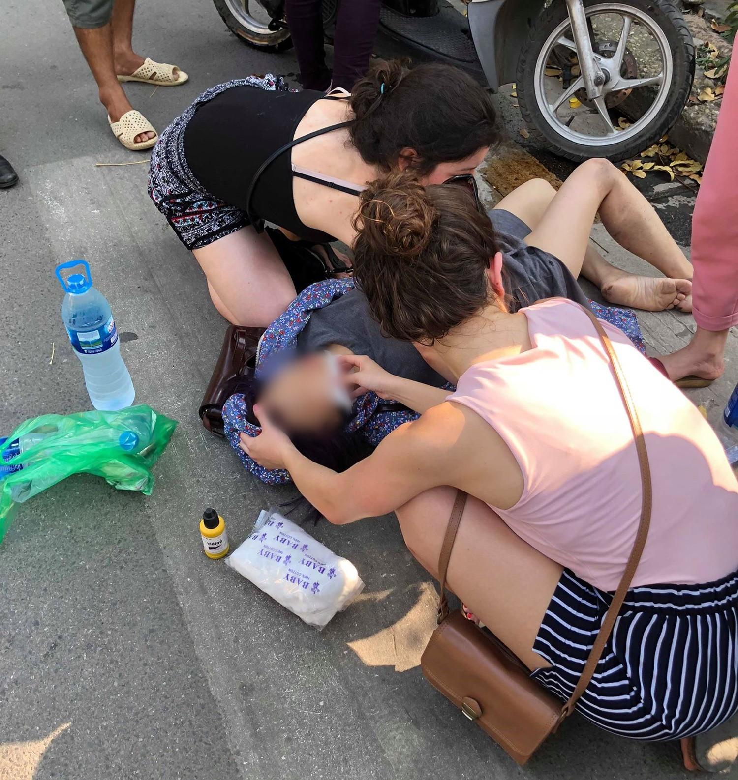 Hà Nội: Nghi say nắng, cô gái tự lao xe vào cột biển báo giao thông được 2 nữ du khách nước ngoài sơ cứu - Ảnh 2.