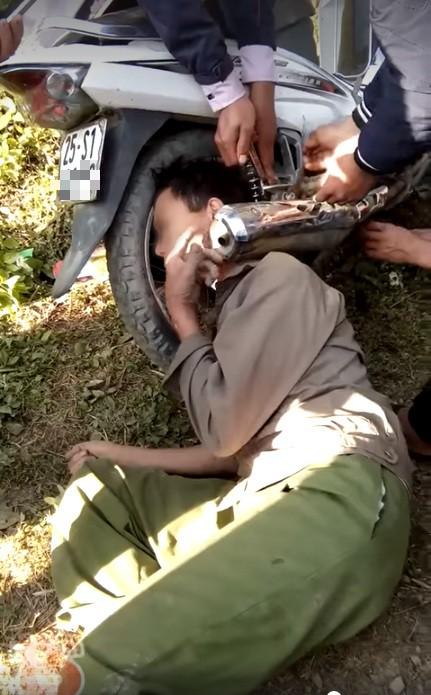 Hy hữu: Người dân giải cứu ông chú bỗng dưng mắc kẹt đầu vào bánh xe máy và ống pô - Ảnh 1.