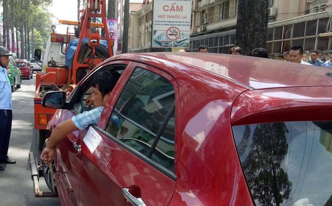 Tài xế cố thủ, hút thuốc trong ô tô dù xe bị kéo đi vì đậu sai quy định - Ảnh 1.