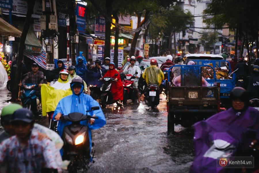 Phụ huynh ẵm bồng con nhỏ, bì bõm lội nước về nhà sau cơn mưa lớn ở Sài Gòn - Ảnh 18.
