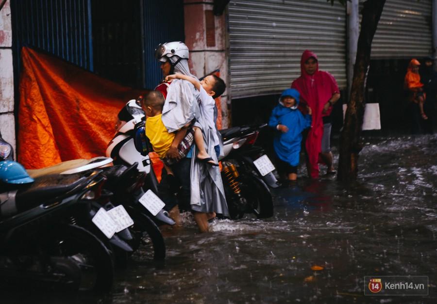Phụ huynh ẵm bồng con nhỏ, bì bõm lội nước về nhà sau cơn mưa lớn ở Sài Gòn - Ảnh 10.