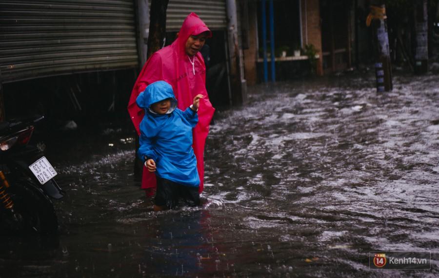 Phụ huynh ẵm bồng con nhỏ, bì bõm lội nước về nhà sau cơn mưa lớn ở Sài Gòn - Ảnh 9.