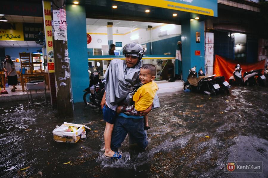 Phụ huynh ẵm bồng con nhỏ, bì bõm lội nước về nhà sau cơn mưa lớn ở Sài Gòn - Ảnh 8.
