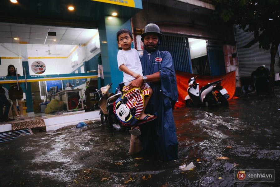 Phụ huynh ẵm bồng con nhỏ, bì bõm lội nước về nhà sau cơn mưa lớn ở Sài Gòn - Ảnh 7.