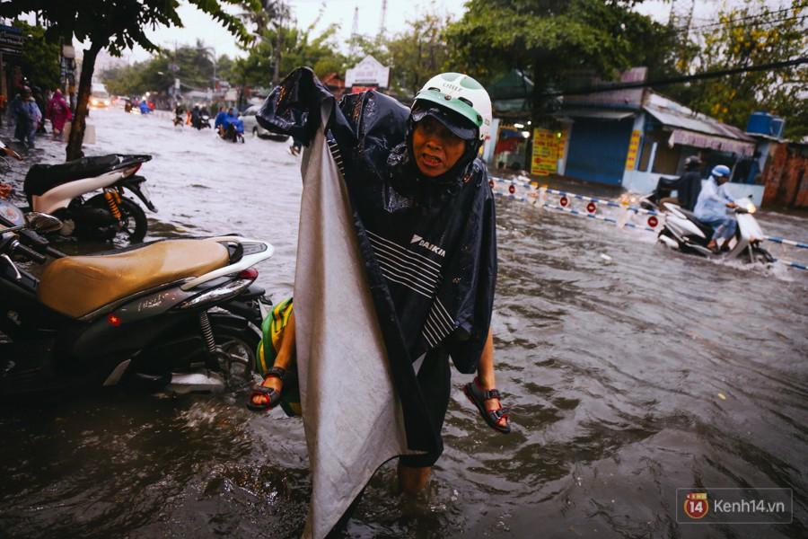 Phụ huynh ẵm bồng con nhỏ, bì bõm lội nước về nhà sau cơn mưa lớn ở Sài Gòn - Ảnh 6.