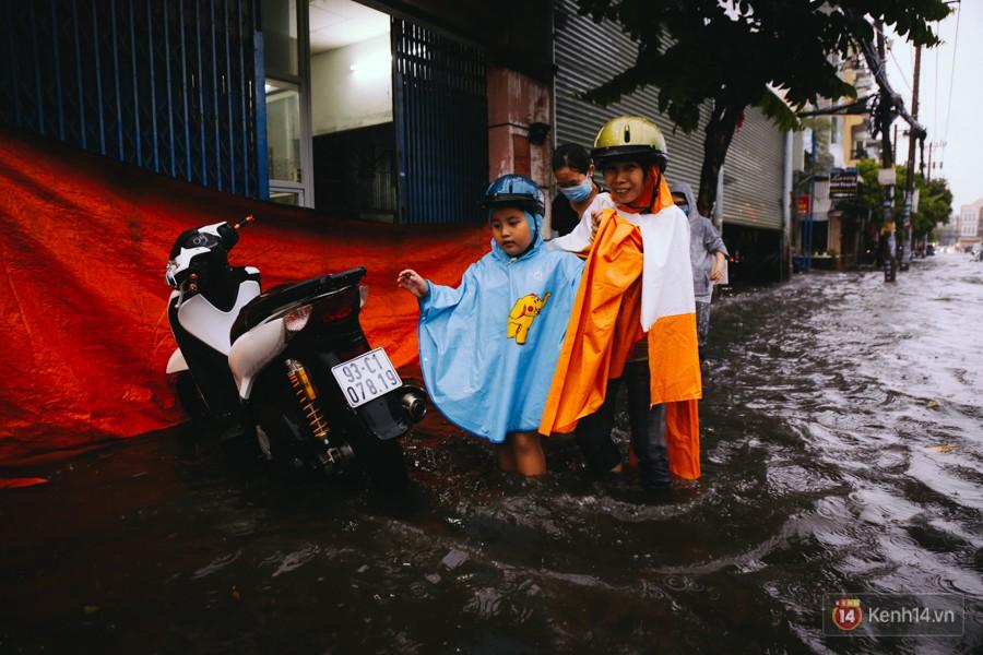 Phụ huynh ẵm bồng con nhỏ, bì bõm lội nước về nhà sau cơn mưa lớn ở Sài Gòn - Ảnh 16.