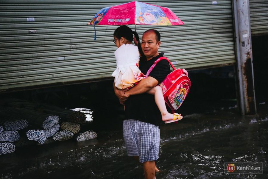 Phụ huynh ẵm bồng con nhỏ, bì bõm lội nước về nhà sau cơn mưa lớn ở Sài Gòn - Ảnh 15.