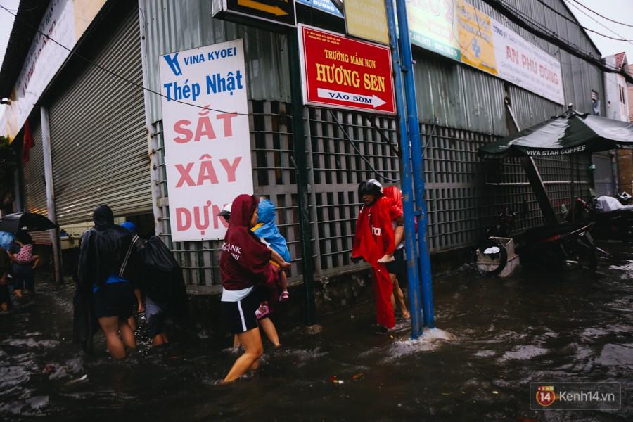 Phụ huynh ẵm bồng con nhỏ, bì bõm lội nước về nhà sau cơn mưa lớn ở Sài Gòn - Ảnh 4.