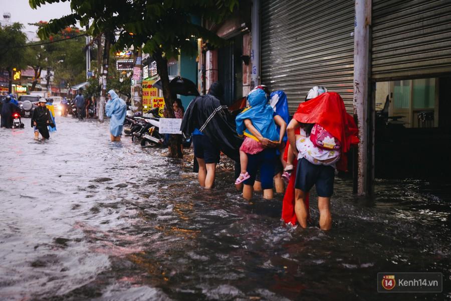 Phụ huynh ẵm bồng con nhỏ, bì bõm lội nước về nhà sau cơn mưa lớn ở Sài Gòn - Ảnh 12.