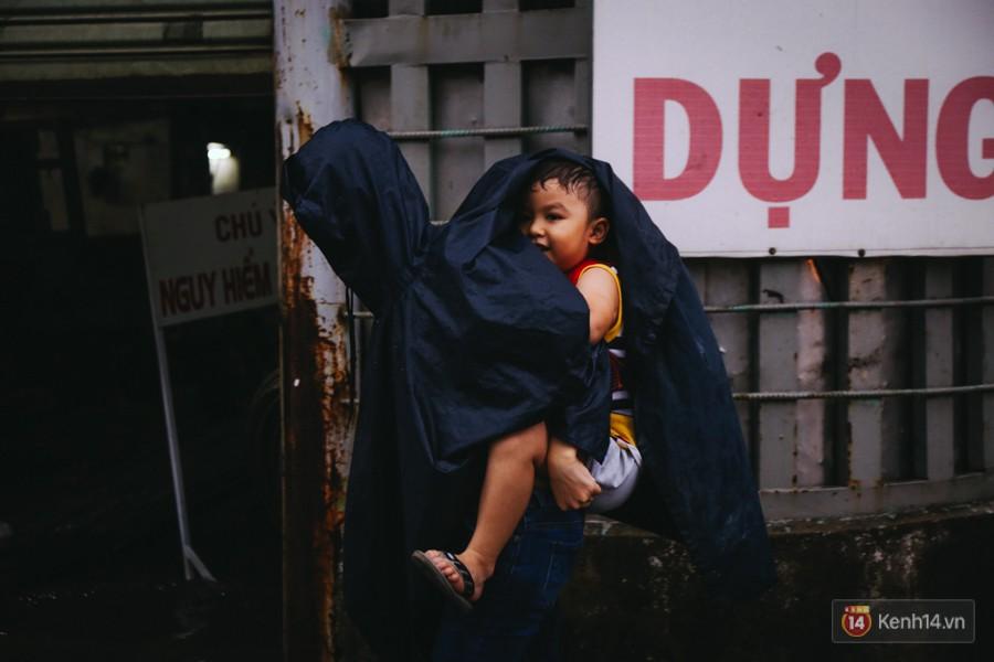 Phụ huynh ẵm bồng con nhỏ, bì bõm lội nước về nhà sau cơn mưa lớn ở Sài Gòn - Ảnh 13.