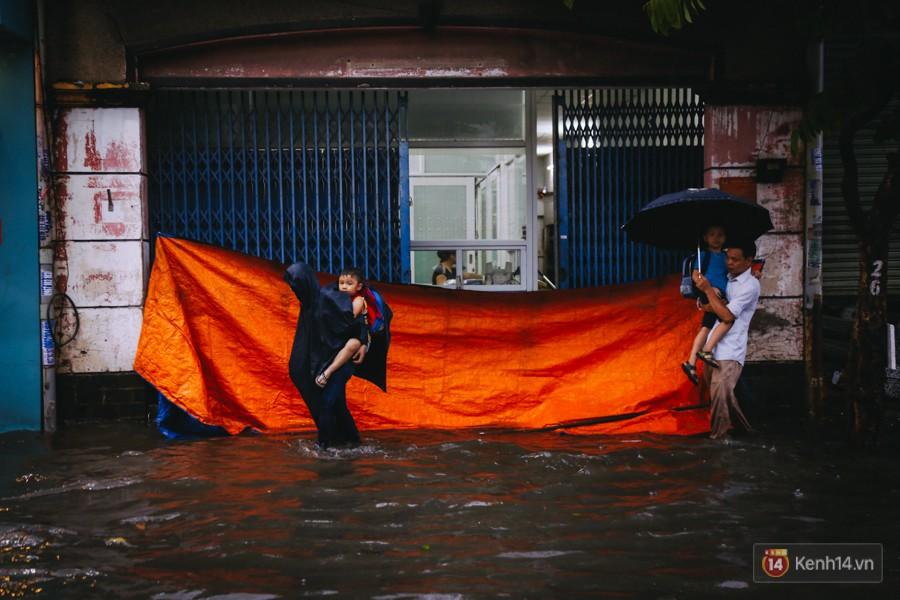 Phụ huynh ẵm bồng con nhỏ, bì bõm lội nước về nhà sau cơn mưa lớn ở Sài Gòn - Ảnh 5.