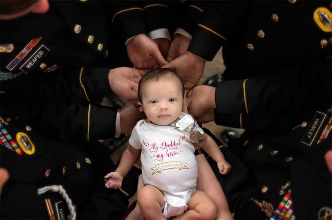 Bức ảnh bé gái được hàng chục người lính nâng đỡ và câu chuyện phía sau khiến mọi người rớt nước mắt - Ảnh 1.