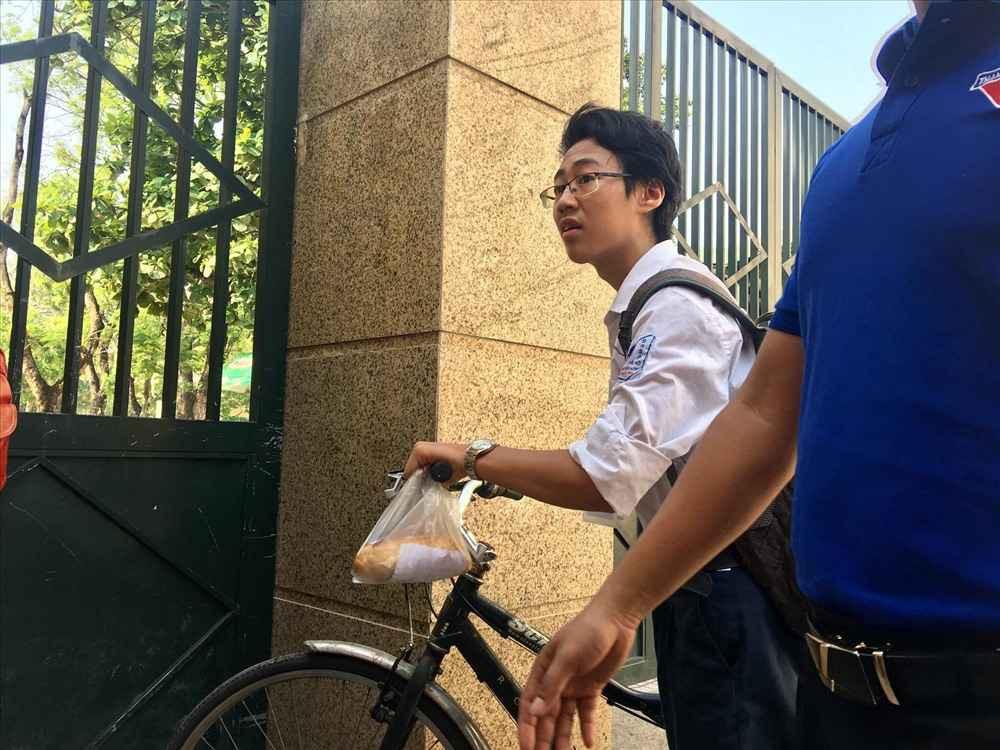 Dân mạng nhiệt tình chia sẻ hình ảnh nam sinh tự đạp xe đến trường thi với chiếc bánh mỳ mua vội treo trên ghi-đông chưa kịp ăn - Ảnh 1.