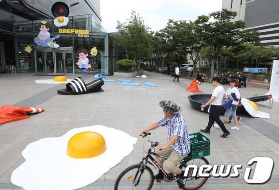 Triển lãm ngoài trời độc đáo chỉ có tại thành phố nóng nhất Hàn Quốc: Trứng rán, dép chảy nhựa đầy đường… kỷ niệm một mùa hè đáng ghét lại đến - Ảnh 1.