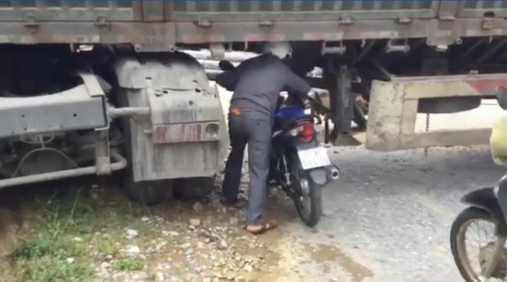 Nhiều người phải dắt xe máy chui dưới gầm để sang phía bên kia.
