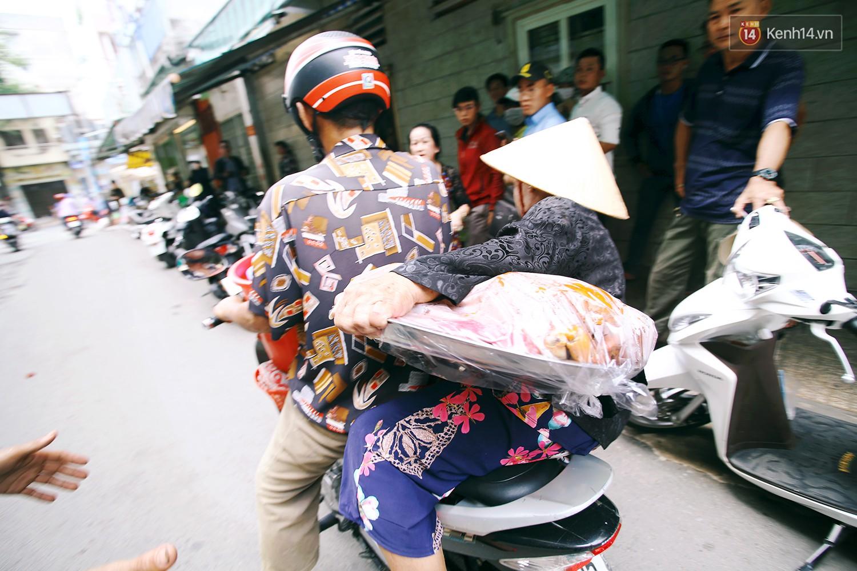 Dì Ba được xe ôm chở tới điểm bán, tay ôm mâm cua to đùng hàng chục con.