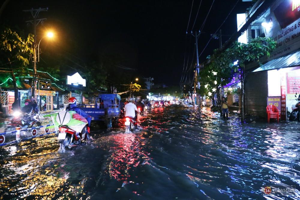 Nữ sinh ở Sài Gòn loạng choạng, suýt té vì ô tô di chuyển tạo sóng trên đường ngập như sông - Ảnh 4.