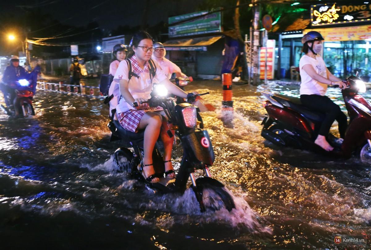 Nữ sinh ở Sài Gòn loạng choạng, suýt té vì ô tô di chuyển tạo sóng trên đường ngập như sông - Ảnh 9.