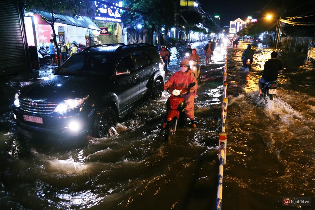 Nữ sinh ở Sài Gòn loạng choạng, suýt té vì ô tô di chuyển tạo sóng trên đường ngập như sông - Ảnh 6.