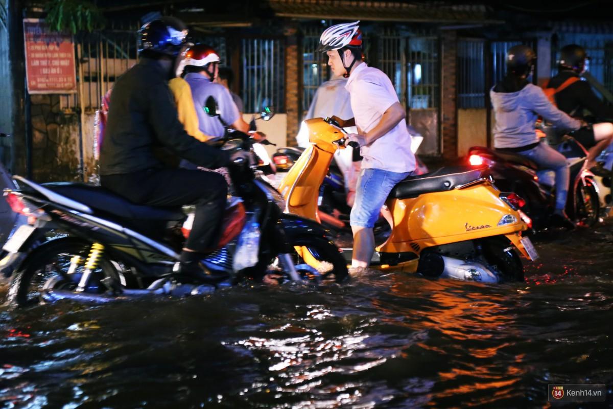 Nữ sinh ở Sài Gòn loạng choạng, suýt té vì ô tô di chuyển tạo sóng trên đường ngập như sông - Ảnh 14.