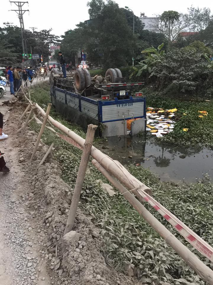 Hà Nội: Xe tải chở bia nằm ngửa dưới mương nước sau khi mất lái - Ảnh 1.