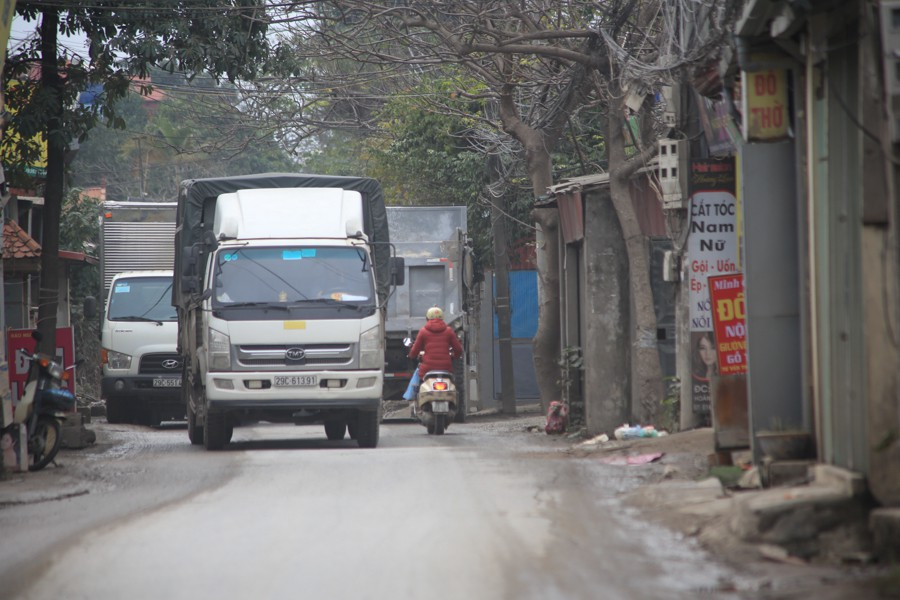 Con đường đau khổ ở Hà Nội bị cày nát, bụi vây kín nhà dân bởi hàng nghìn lượt xe siêu trọng tải mỗi ngày - Ảnh 1.
