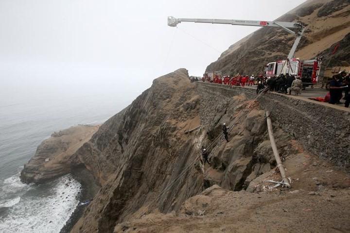 Ảnh: Gian nan cứu hộ chiếc xe bus lao xuống vực sâu cạnh biển ở Peru - Ảnh 2.