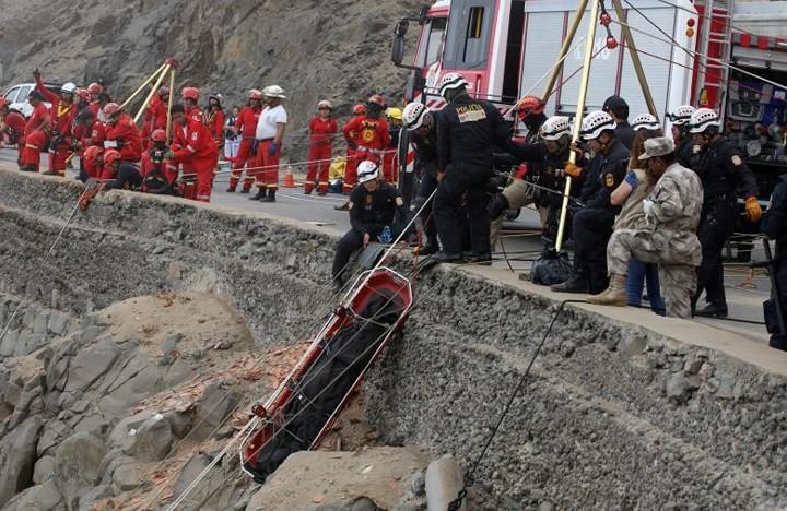 Ảnh: Gian nan cứu hộ chiếc xe bus lao xuống vực sâu cạnh biển ở Peru - Ảnh 3.