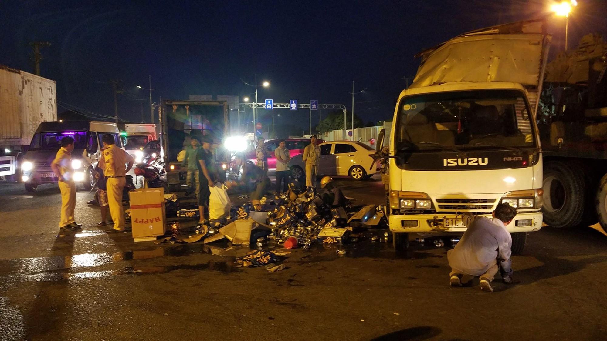 TP.HCM: Xe tải chở bia lật giữa đường, người dân giúp tài xế thu gom - Ảnh 3.