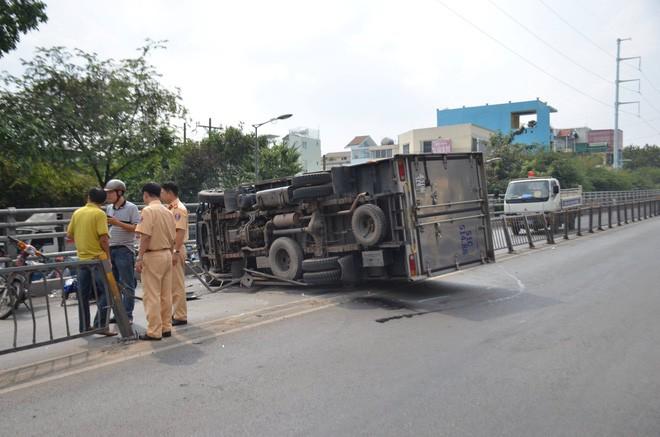 TP. HCM: Xe tải lật ngang trên cầu vượt trúng 2 xe máy, 3 người bị thương - Ảnh 1.