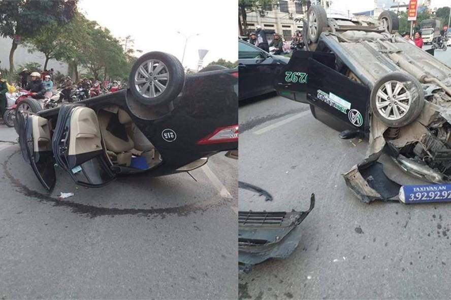Người dân cạy cửa xe taxi lật ngửa cứu 2 người bị thương - Ảnh 1.