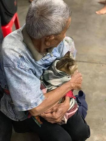 Cụ ông gây xúc động khi ôm khư khư chú mèo cưng đi tránh cơn bão lớn nhất 3 thập kỷ ở Thái Lan - Ảnh 3.