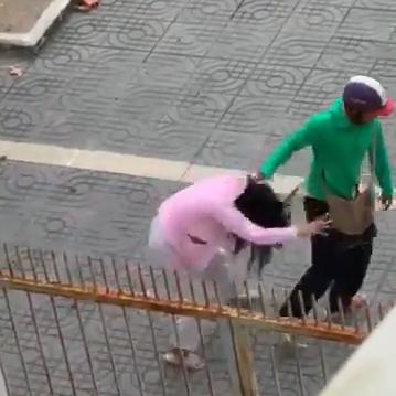 Người đàn ông túm tóc vợ mình rồi ấn xuống vỉa hè (Ảnh cắt từ clip)