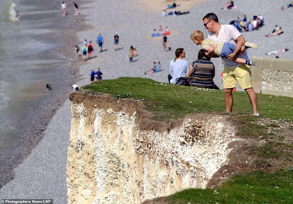 Sống ảo tối thượng: Ông bố bế con nhỏ đung đưa trên vách đá dựng đứng hơn 120m chỉ để chụp ảnh - Ảnh 1.