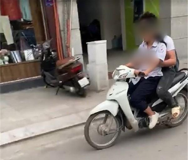 Clip: 2 học sinh không đội mũ bảo hiểm và bàn tay thân mật đến phản cảm của nam sinh ngồi sau xe máy - Ảnh 2.