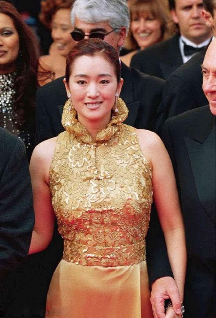 Bộ sườn xám màu vàng hoàng kim đã giúp Củng Lợi đẹp như nữ hoàng cao sang quyền quý tại thảm đỏ LHP Cannes 1999. Đại mỹ nhân tiếp tục trung thành với mái tóc búi gọn gàng chuẩn mực cùng lối trang điểm tông nude nền nã.