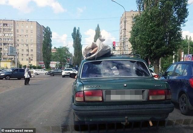 Chỉ có ở Nga: Xác chết được để lên nóc xe hơi chở đi khắp phố khiến người dân khiếp đảm - Ảnh 1.