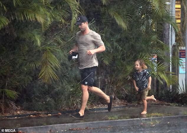 Ông bố phũ của năm: Cùng dầm mưa nhưng Thor Chris Hemsworth đội mũ đi giày, để con trai đầu trần chân đất - Ảnh 3.