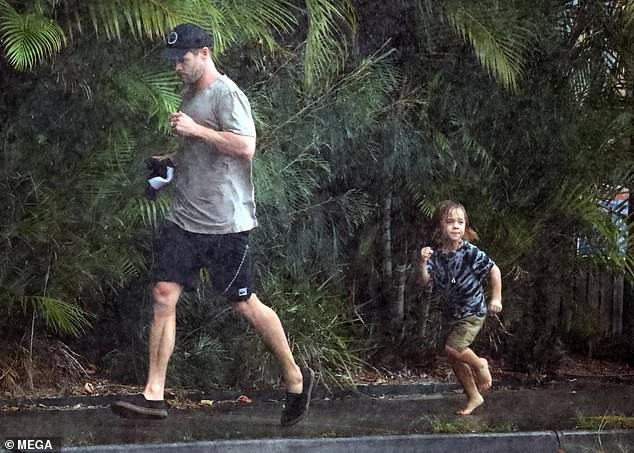 Ông bố phũ của năm: Cùng dầm mưa nhưng Thor Chris Hemsworth đội mũ đi giày, để con trai đầu trần chân đất - Ảnh 4.