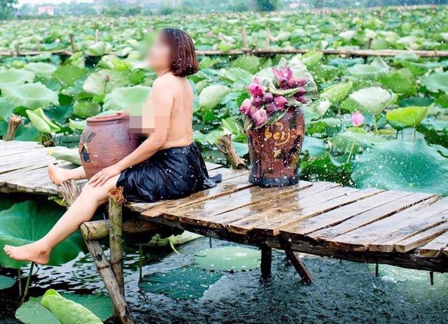 Hình ảnh người phụ nữ trung niên khoe ngực trần, ngồi ôm chum chụp ảnh bên hồ sen bị ném đá dữ dội - Ảnh 1.