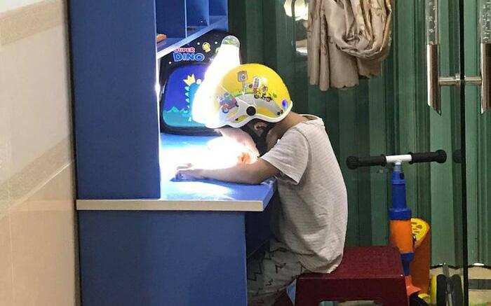 Sự thật đằng sau cảnh học sinh lớp 1 phải đội mũ bảo hiểm ngồi làm bài tập khi bố mẹ đứng cạnh