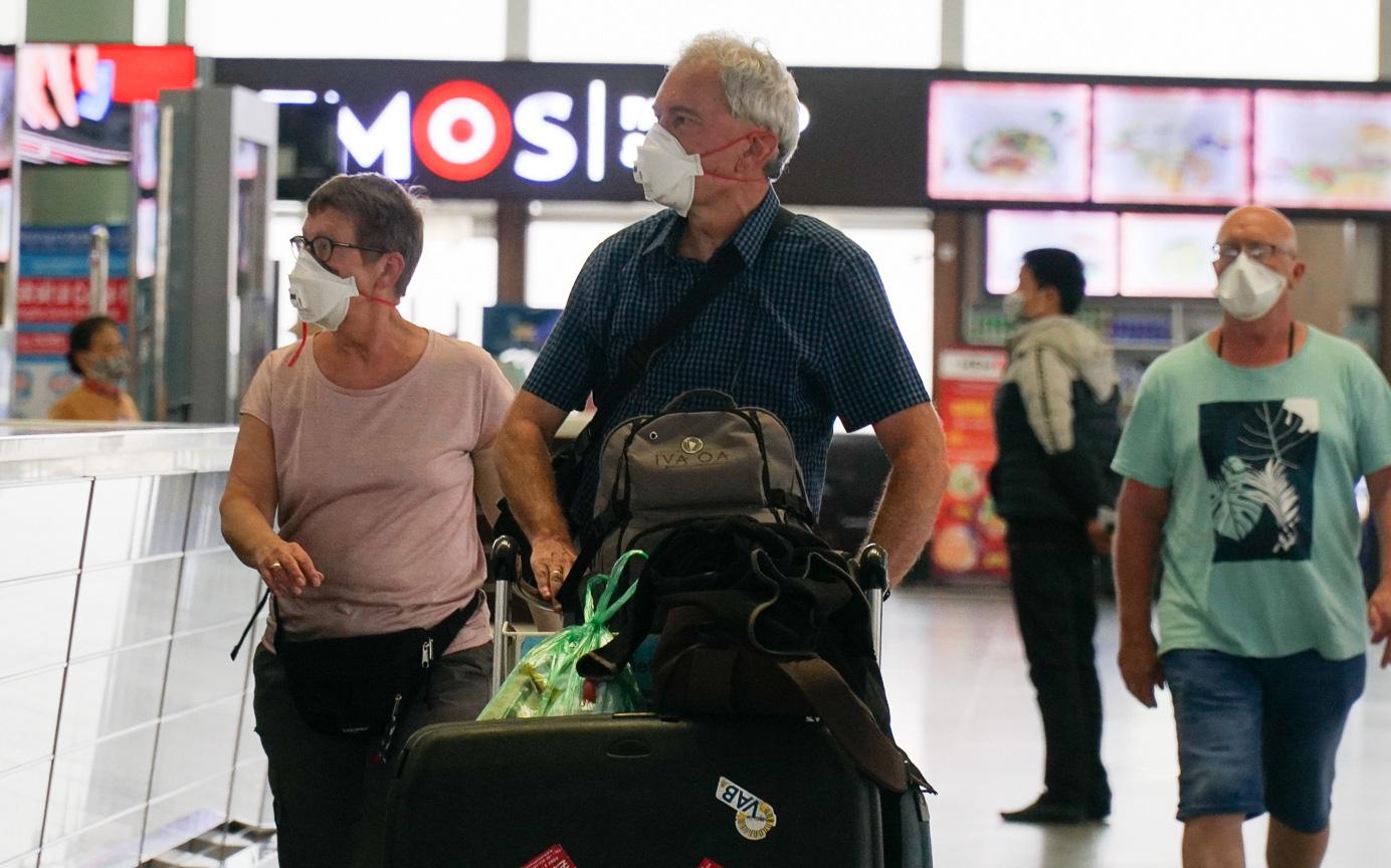 Chùm ảnh: Khách nước ngoài tuân thủ quy định đeo khẩu trang khi đến sân bay quốc tế Nội Bài
