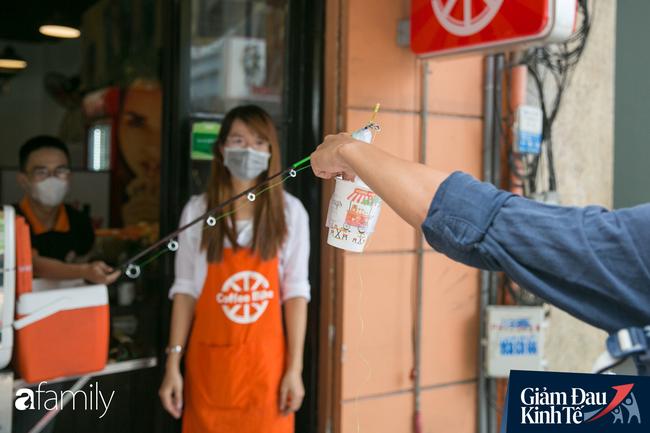 Nhiều quán ăn, cà phê ở Sài Gòn chuyển mình thời Covid-19, học theo Ấn Độ khoanh vùng an toàn cho khách đứng, dùng cả cần câu xa 2m để đưa hàng cho shipper - Ảnh 7.