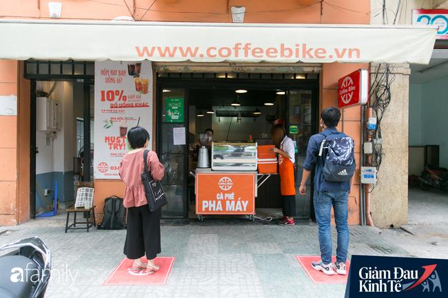 Nhiều quán ăn, cà phê ở Sài Gòn chuyển mình thời Covid-19, học theo Ấn Độ khoanh vùng an toàn cho khách đứng, dùng cả cần câu xa 2m để đưa hàng cho shipper - Ảnh 2.