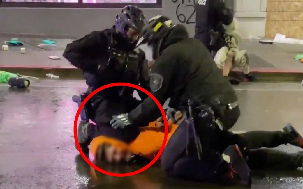 Cảnh sát Mỹ ghì cổ để khống chế người 'hôi của' trong cuộc biểu tình nhưng được đồng nghiệp ngăn cản kịp thời
