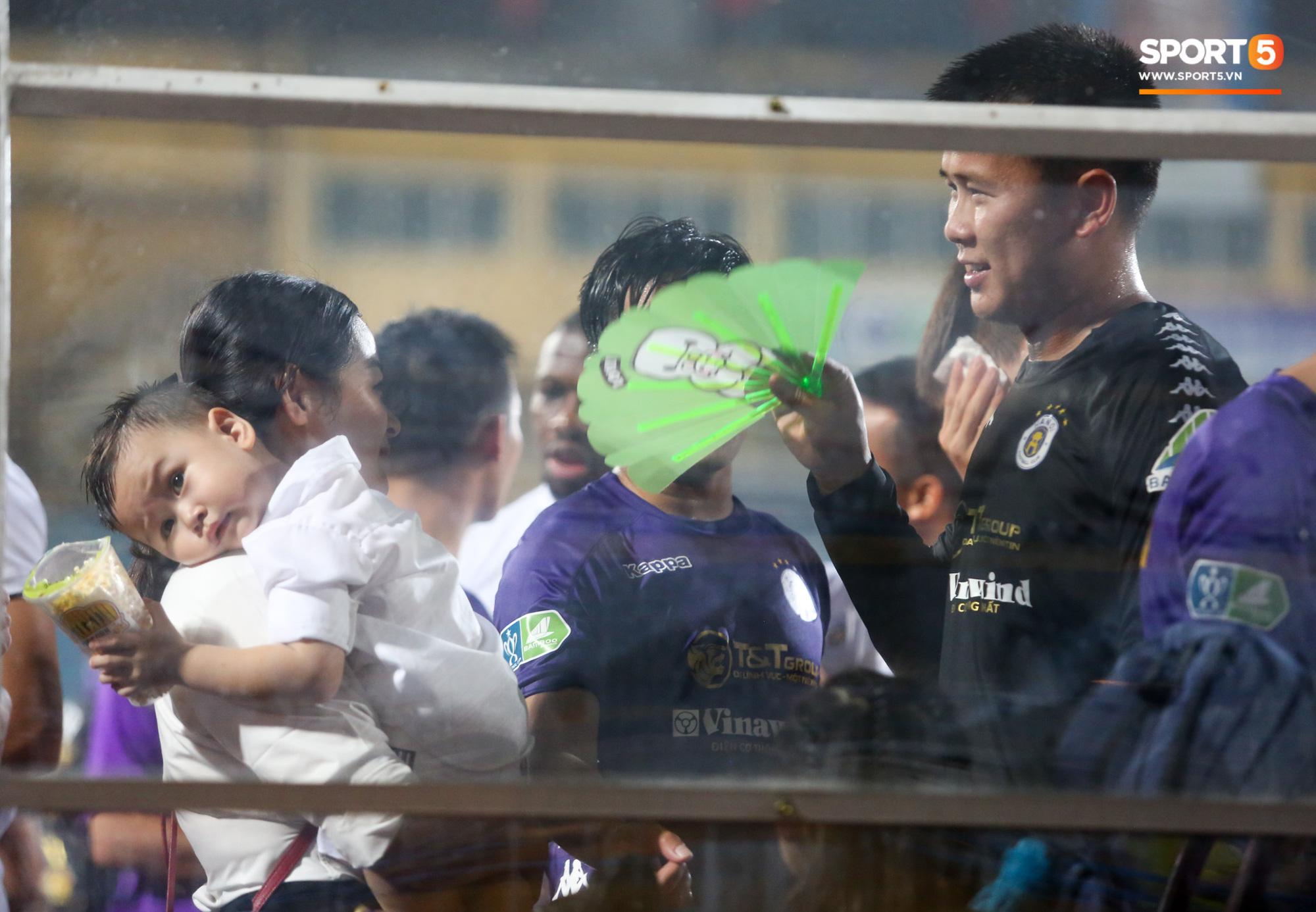 Hình ảnh đàn anh Duy Mạnh cần mẫn đứng quạt cho vợ và con gái, mặc kệ đồng đội ở Hà Nội FC ăn mừng - Ảnh 1.