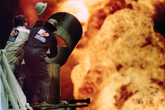 Lính cứu hỏa nỗ lực cắt một phần đường ống và khống chế đám cháy tại giếng dầu ở Kuwait năm 1991. Bức ảnh của nhiếp ảnh gia Russell Boyce cho thấy cảnh đám lửa cháy rực và vụ nổ đã thổi bay mũ bảo hiểm của một lính cứu hỏa.